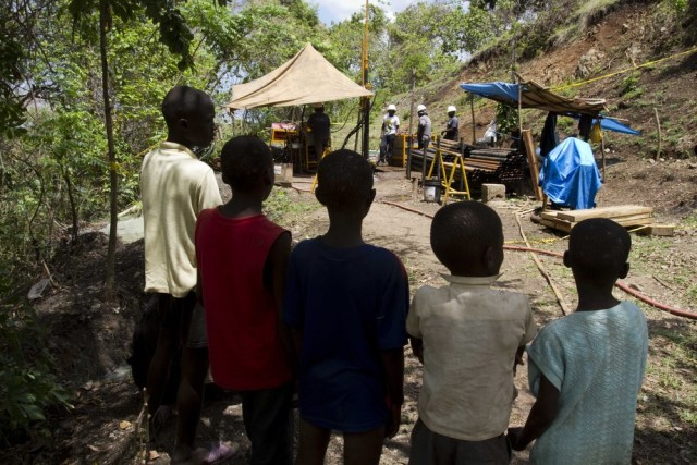 Image: Haitian children watch gold drilling
