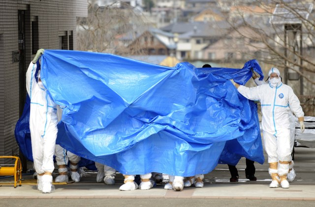 Image: Nuclear plant workers shielded with tarps in Fukushima, Japan