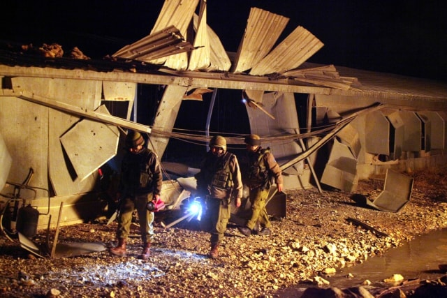 Image: Israeli soldiers examine damage after a rocket fired from Lebanon hit a chicken coop