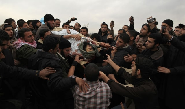 Image: Palestinians carry the body of militant Muaman Abu-Daf in Gaza City
