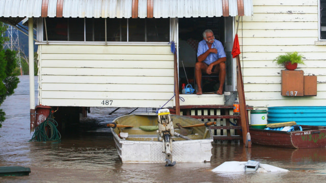 Image: Man in home surrounded by floodwaters