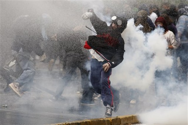 Image: A demonstrator throws a stone at riot police Thursday during a demonstration in Santiago, Chile.