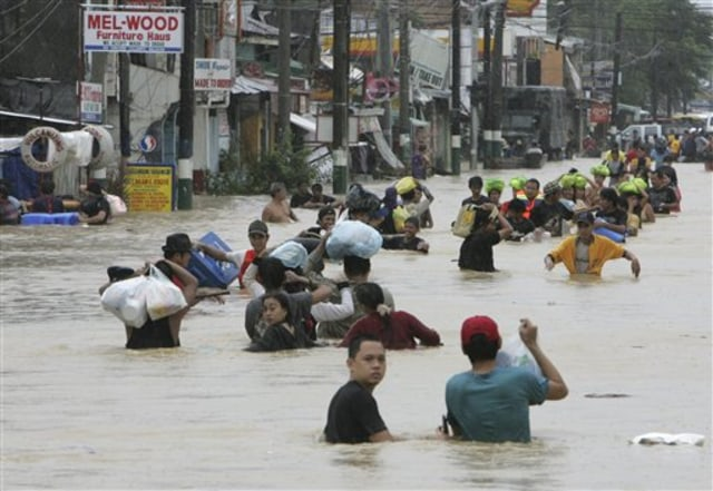 Image: Residents evacuate to safer grounds as massive flooding continues for the second day Saturday at Calumpit township, Bulacan province north of Manila, Philippines.