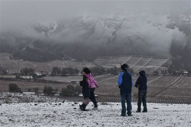 Image: Children play during an unusual snowfall in the Atacama desert, near Copiapo, Chile, Sunday, Sunday.