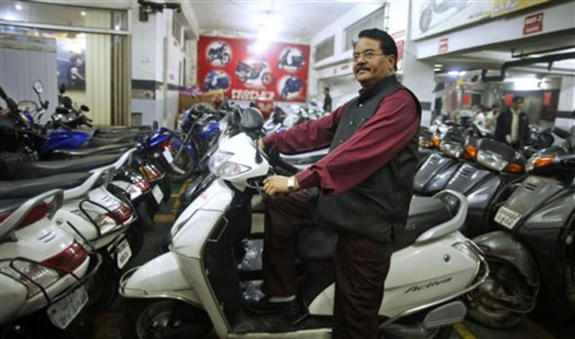 Image: Hari Kishan Pippal checks out a scooter inside his Honda dealership showroom in Agra, India.