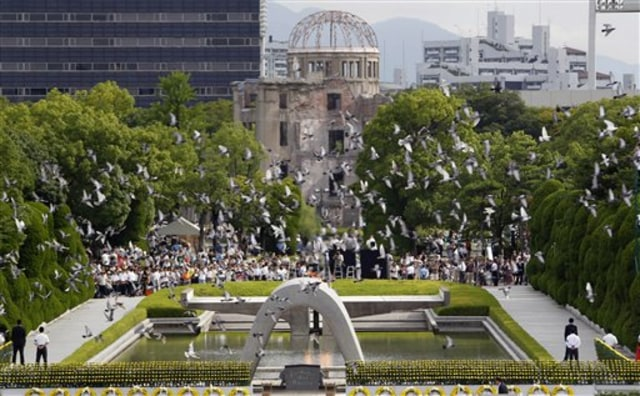 image: Doves fly by the gutted Atomic Bomb Dome, center in background, preserved as a landmark for the tribute to the A-Bomb attack on Hiroshima in 1945.