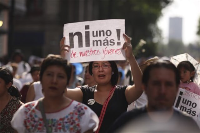 "A protester in Mexico carries as sign saying ""Not one more of our young men!"""