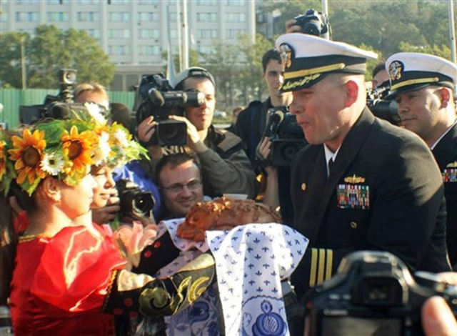 Image: U.S. Navy, Cmdr. Joseph R. Darlak is shown taking a bite of a traditional offering of bread and salt after arriving in Vladivostok, Russia.