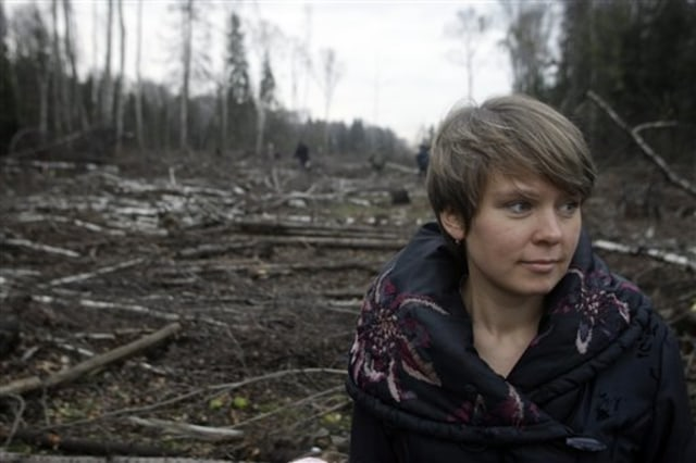 Image: Activist stands in cleared area of forest
