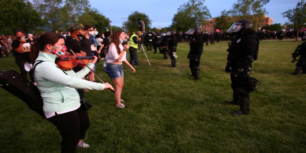 Riot police confront peaceful violin vigil for Elijah McClain with pepper spray