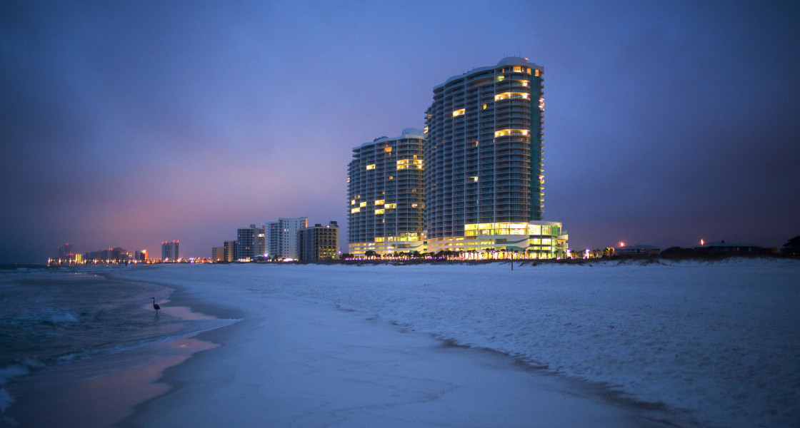 Image: The Turquoise Place condominium buildings rise above Orange Beach, Alabama, before sunrise.