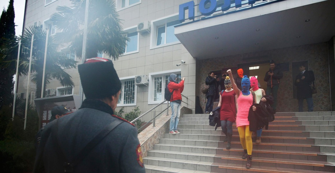 Image: Masked members of Pussy Riot leave a police station in Adler during the 2014 Sochi Winter Olympic