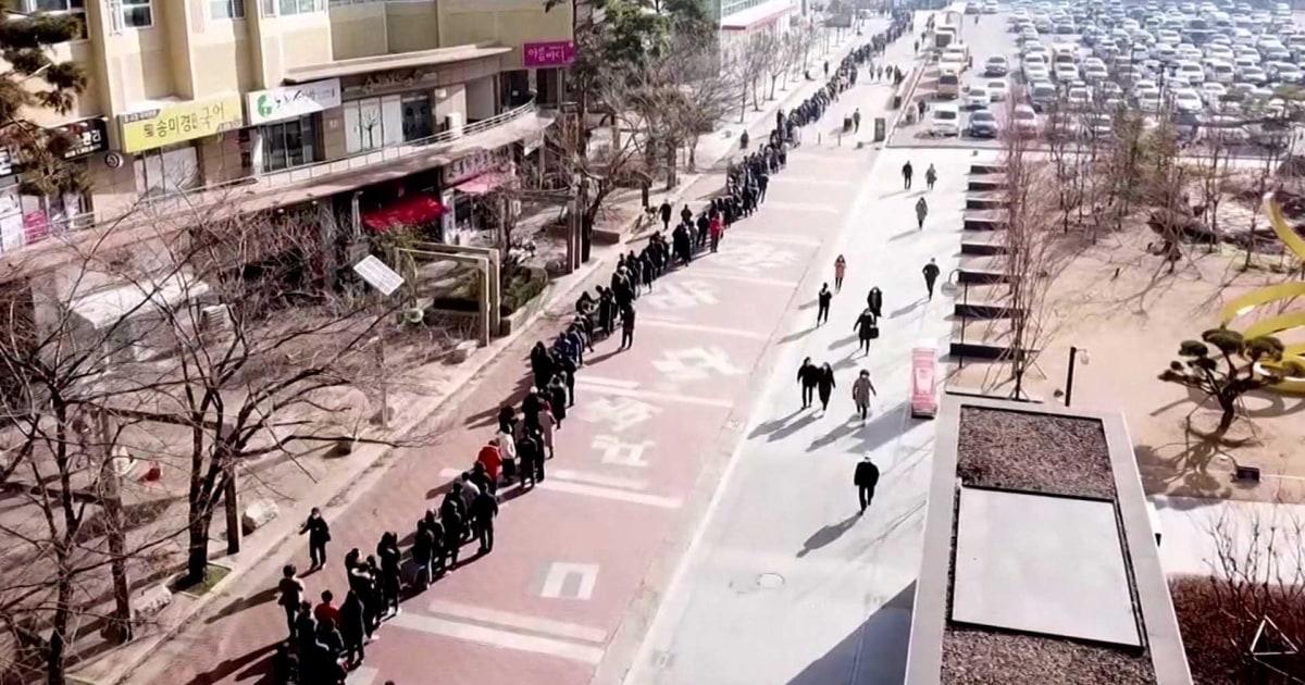 Hundreds fearing coronavirus stand in line for face masks
