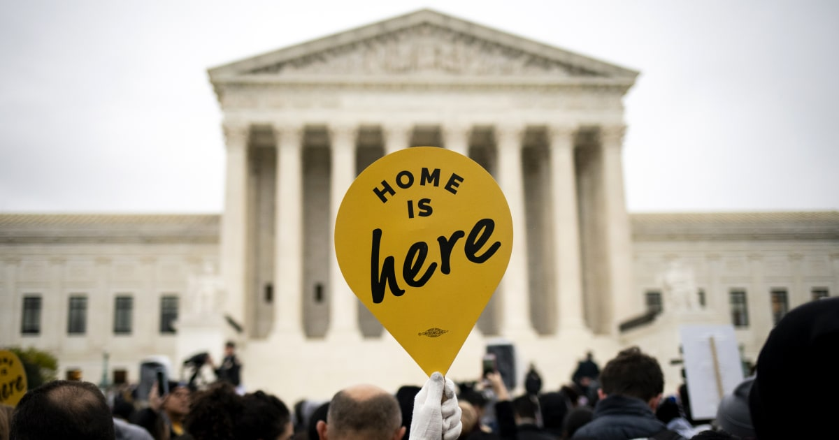 A protestor holds up a yellow sign in the shape of a pin that says 'Home is Here'