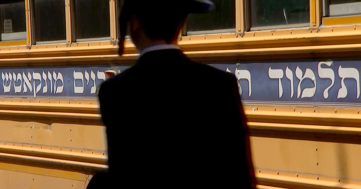 An Orthodox Jewish man walks in front of a school bus in the predominantly Hasidic neighborhood of Borough Park in Brooklyn, N.Y.NBC News