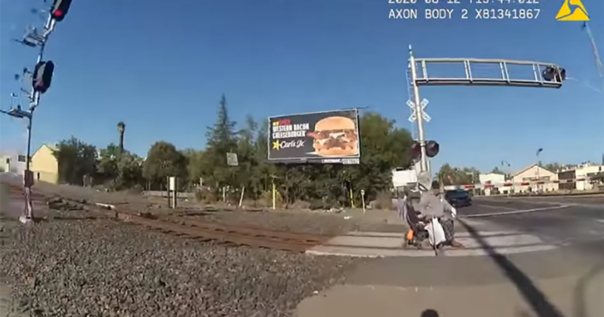 Video shows police officer pulling man in wheelchair off railroad tracks before oncoming train hits – NBC News