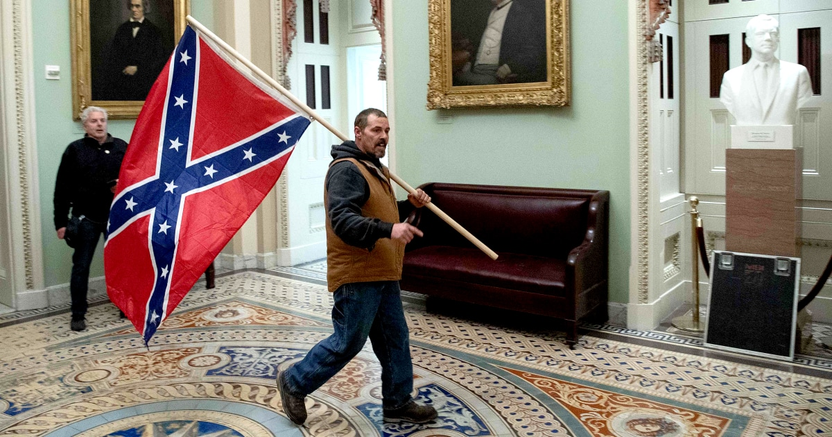 Man holding Confederate flag in Capitol during pro-Trump riot turns himself in thumbnail