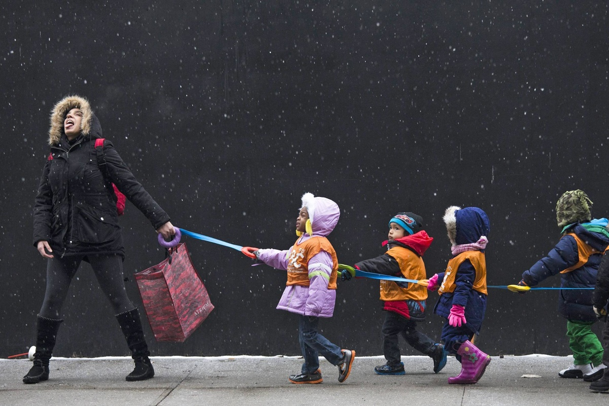 Image: A school teacher, who wished to stay unidentified, attempts to catch snowflakes while leading her students to a library from school in the Harlem neighborhood of New York