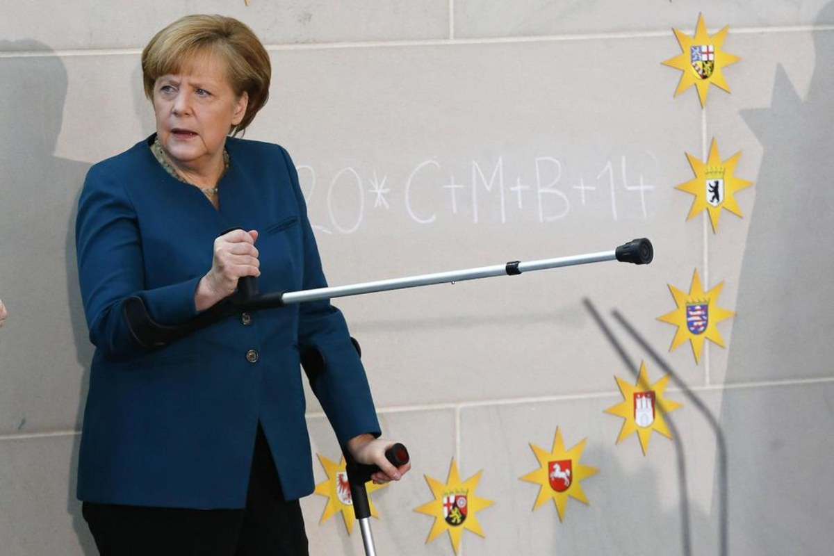 Image: German Chancellor Merkel gestures with crutch as she meets carol singers during reception at Chancellery in Berlin