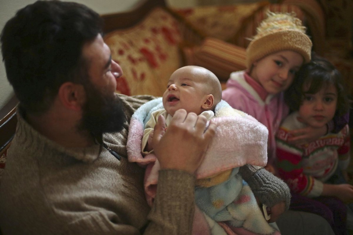 Image: Abu Rateb Malis holds his 27-day-old son Rateb Malis at a relative's home in the Duma neighborhood of Damascus