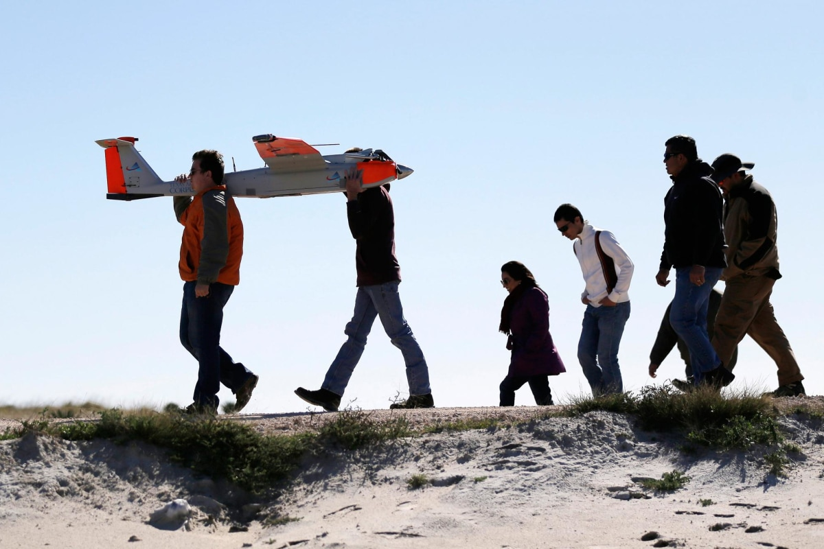 Image: Crew members carry a drone with the wing span of almost 13 feet following a test flight