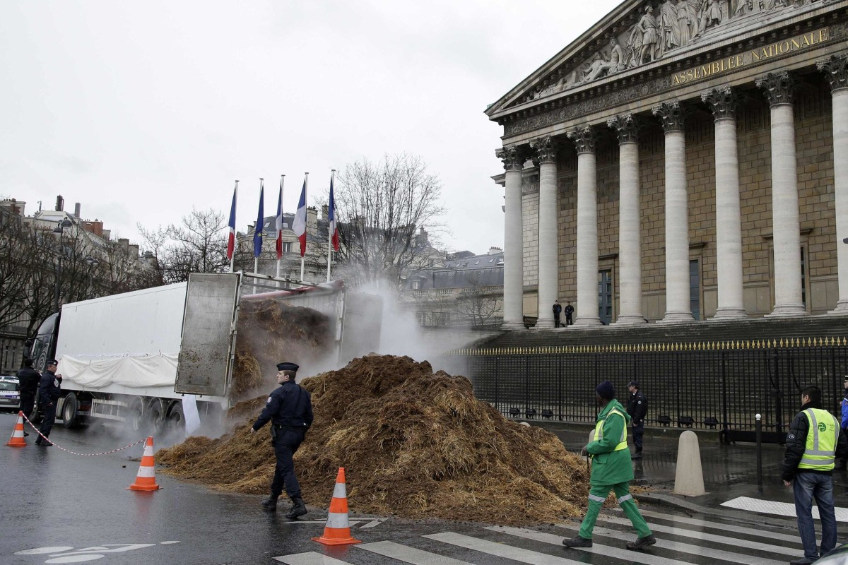 Image: French police and municipal workers walk near a large pile of manure sits in front of the National Assembly in Paris.