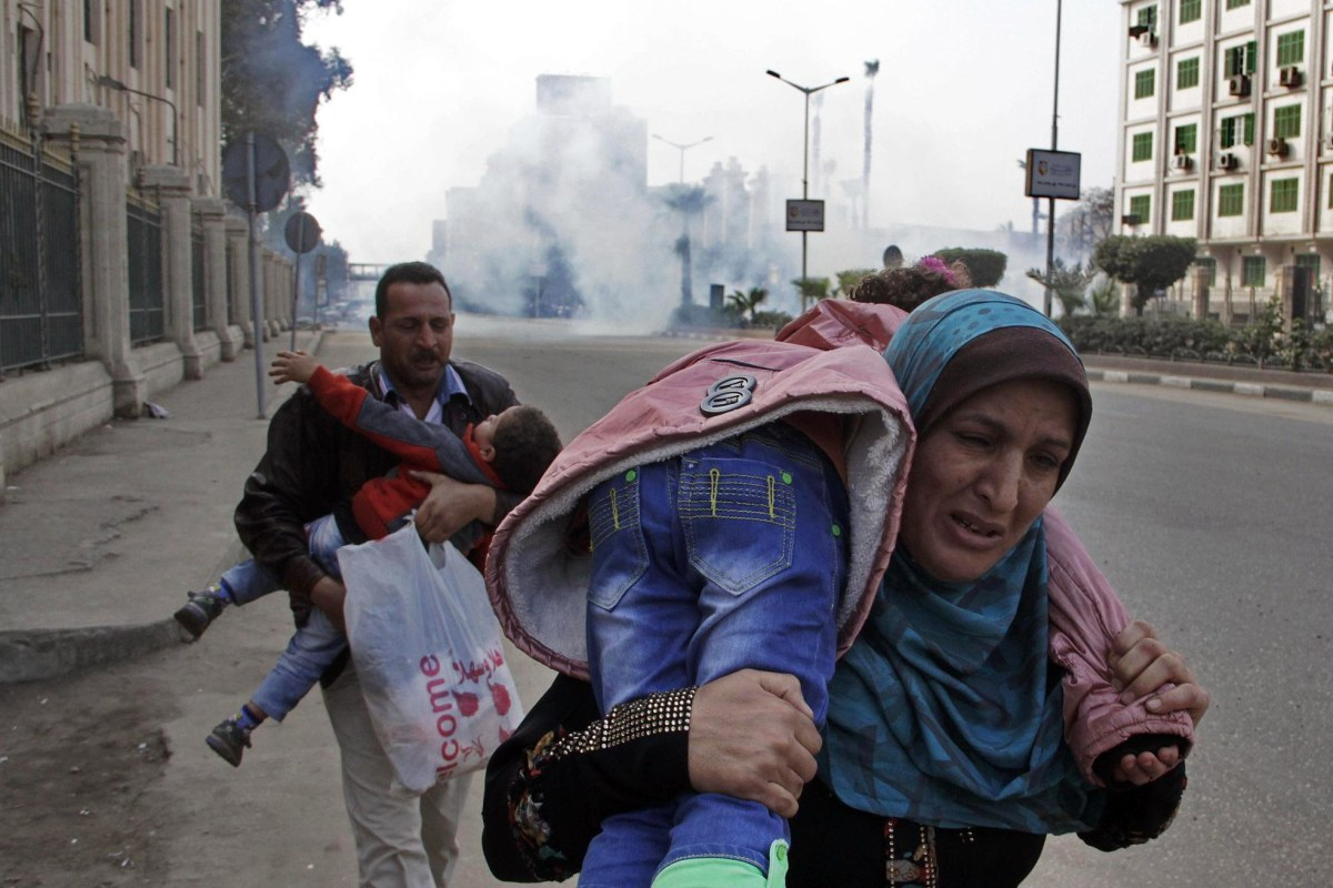 Image: A family runs away from tear gas during clashes in Cairo.