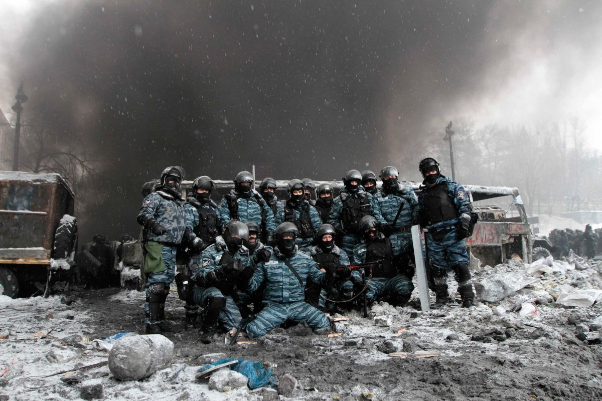 Image: Riot police officers pose for a picture near burnt vehicles as smoke rises in the background during clashes with pro-European protesters in Kiev