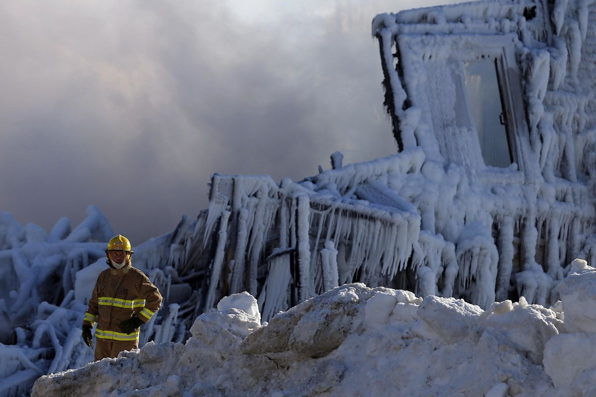 Image: A firefighter looks on at the seniors complex Residence du Havre after a fire in L'Isle Verte, Quebec