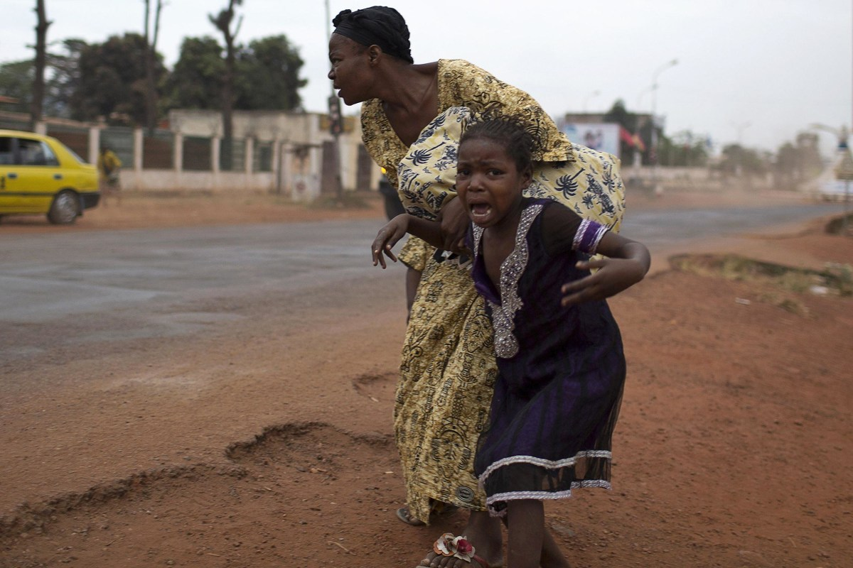 Image: A mother holds her child while attempting to take cover as repeated gun shots are heard close to Miskine district during continuing sectarian violence in the capital Bangui