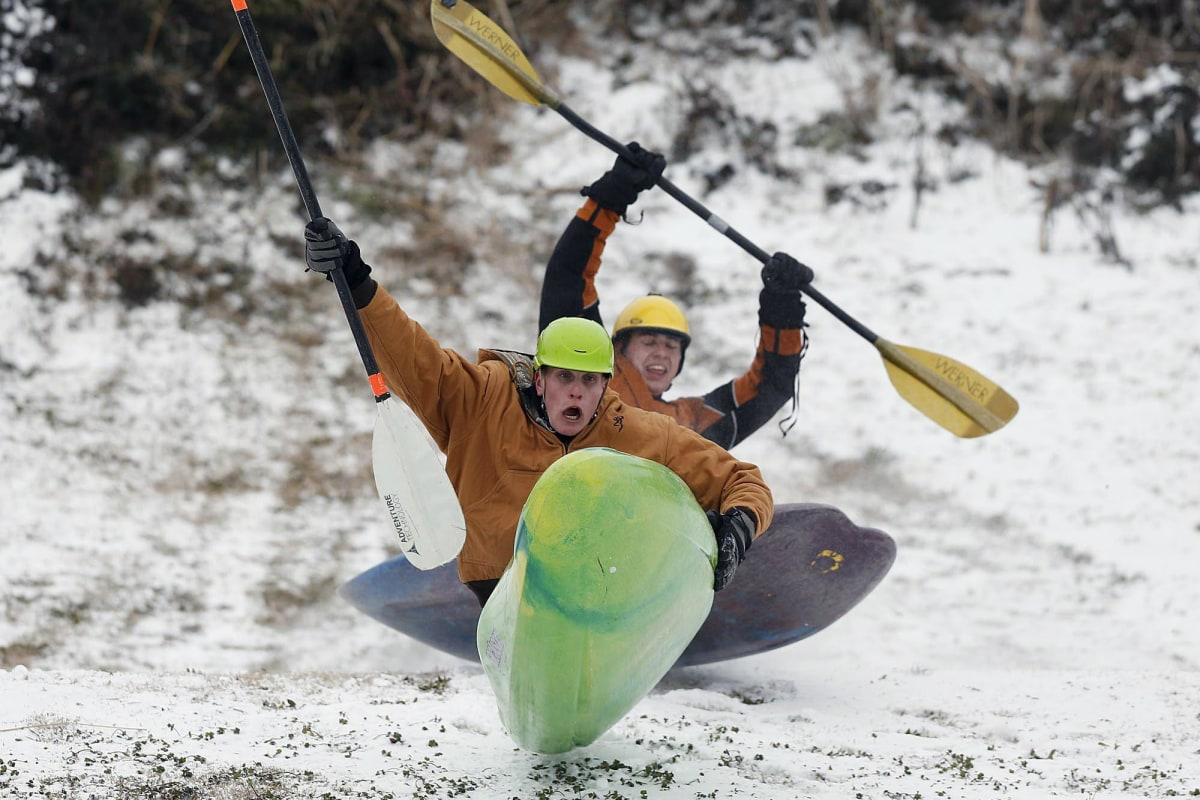 Image: Brent LaForte, front, and Brian Bartlett, rear, grab some air as they slide down a hill in a kayak in downtown Tuscaloosa, Ala.