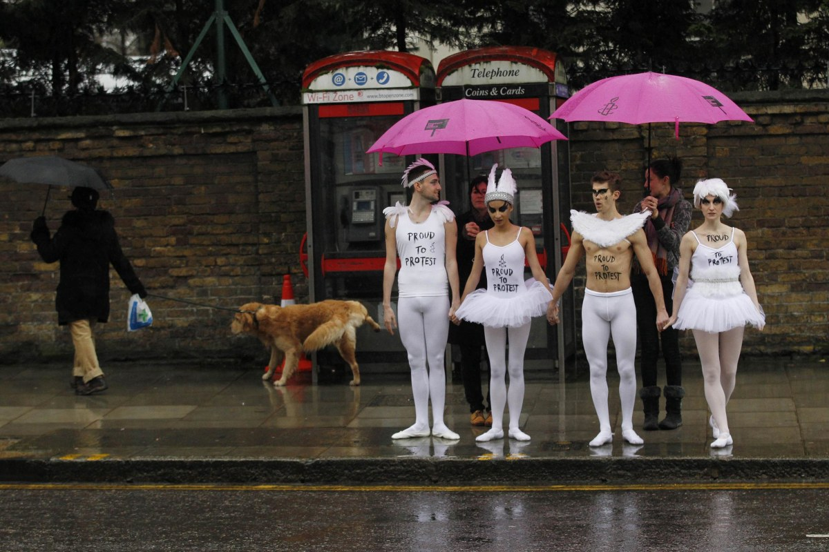 Image: Human rights campaigners dressed as ballet dancers wait to cross a road