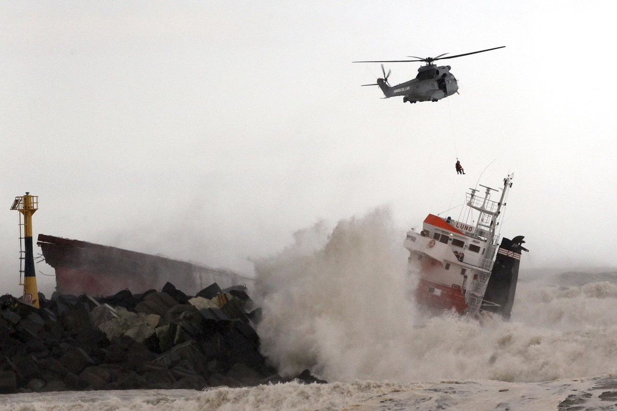 Image: A helicopter lowers a rescue worker toward a Spanish cargo ship