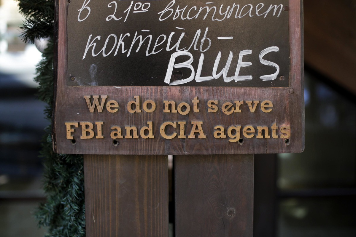 "Image: A sign that says ""We do not serve FBI and CIA agents,"" hangs outside a restaurant"