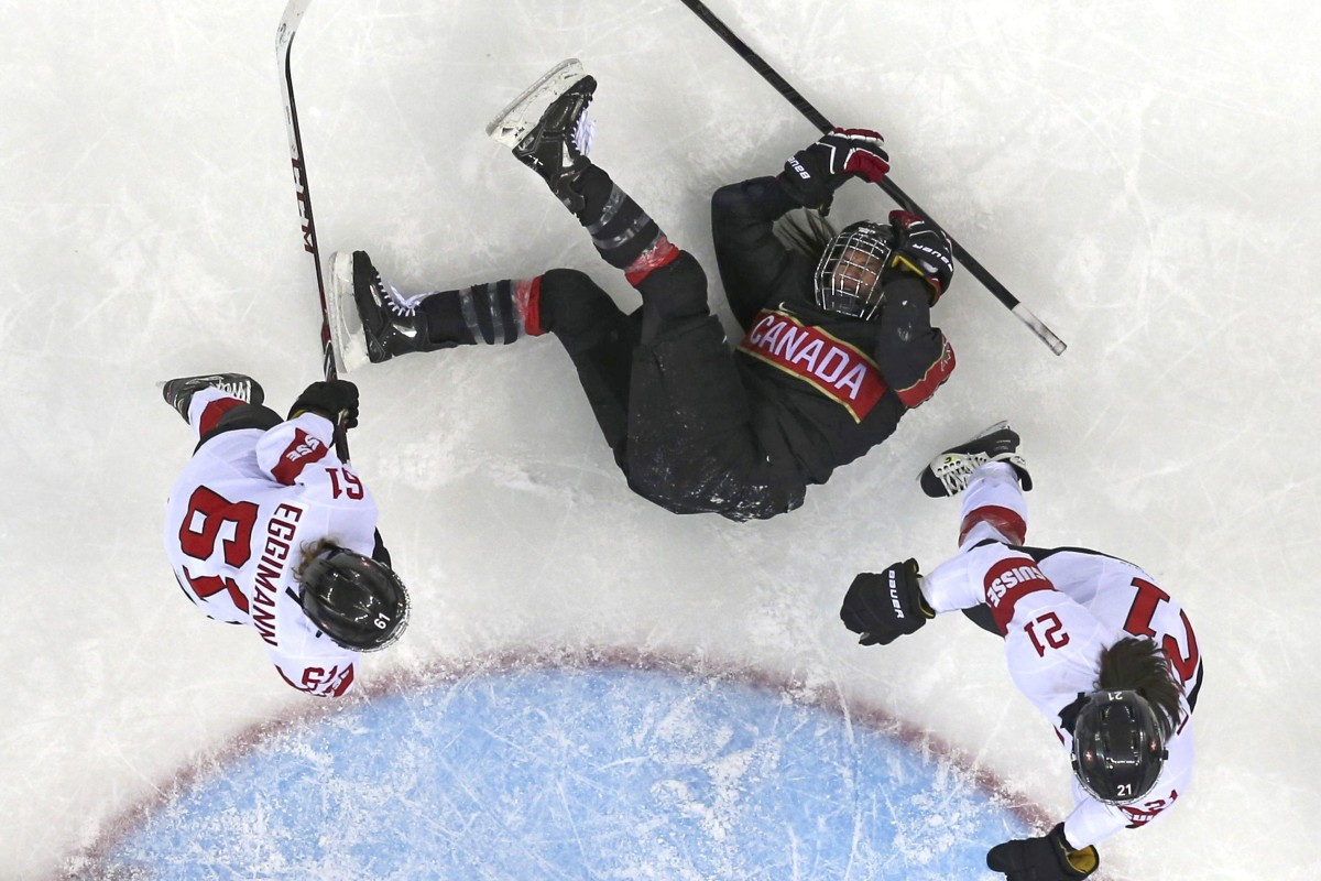 Canada's Spooner is knocked to the ice by Switzerland's Eggimann and Benz during the second period of their women's ice hockey game at the 2014 Sochi Winter Olympics