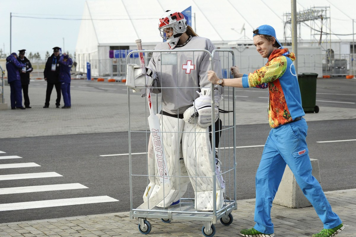 Image: A volunteer transports Switzerland's women Ice Hockey team goalkeeper Florence Schelling to a practice session during the Sochi Winter Olympics on February 9, 2014.