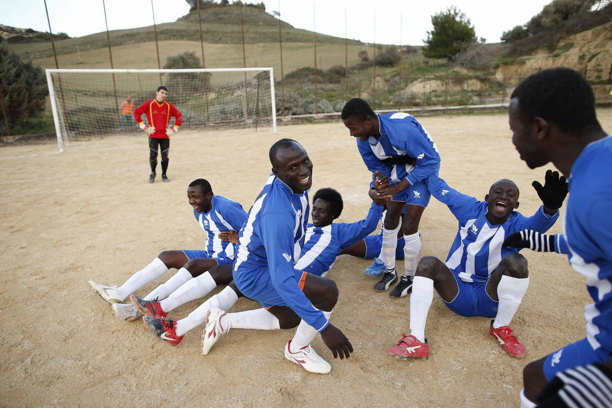 Image: African migrants, who are members of the ASD Mineo soccer team, celebrate after scoring against Massiminiana in the Sicilian village of Mineo