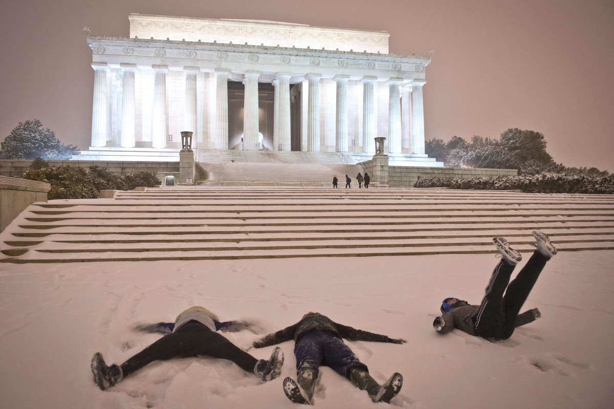 Image: Young people make 'snow angels' in front of the Lincoln Memorial as a heavy snow storm hits Washington, D.C., early Thursday.