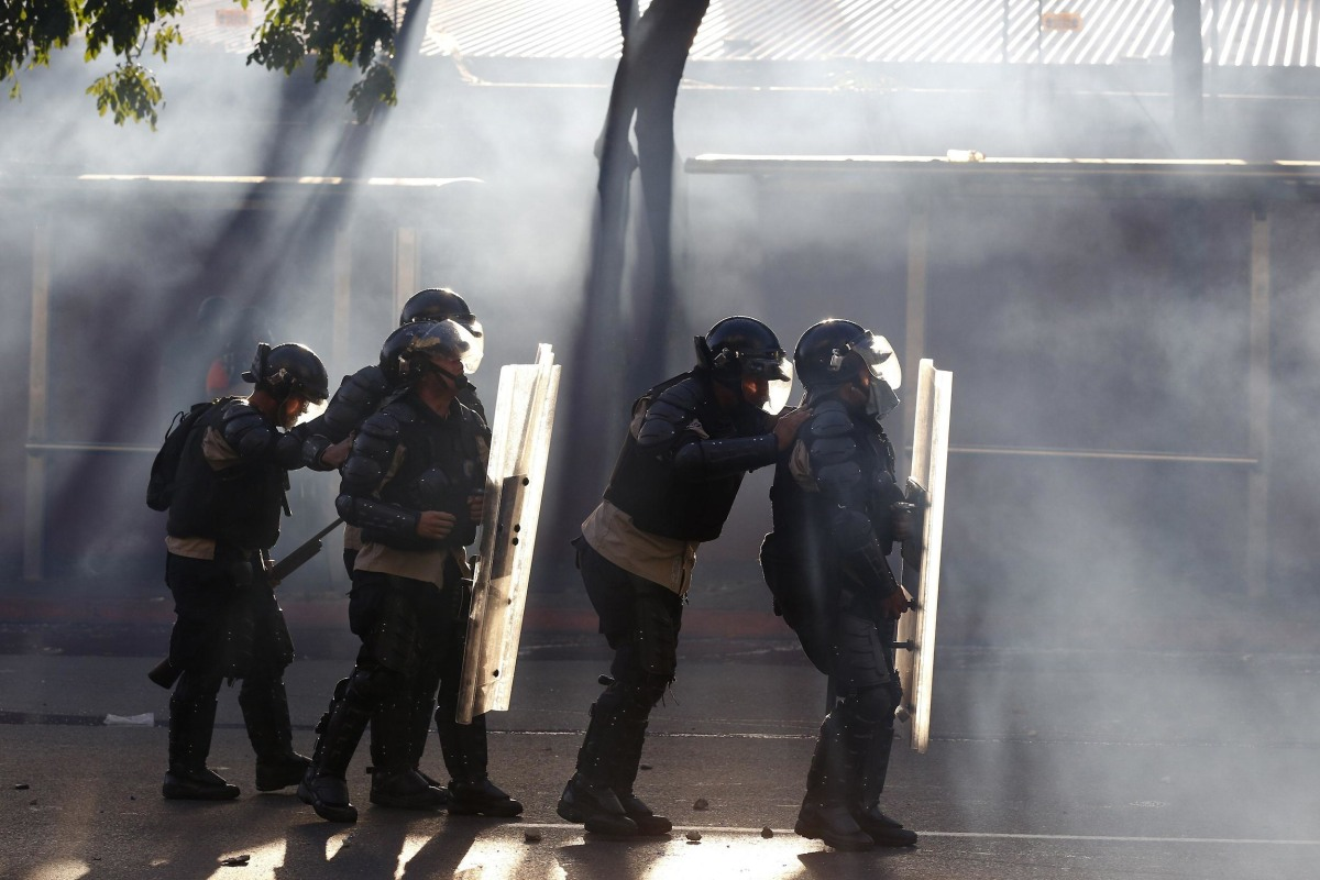 Image: Riot police is seen among tear gas as they fight against students during a protest against Nicolas Maduro's government in Caracas