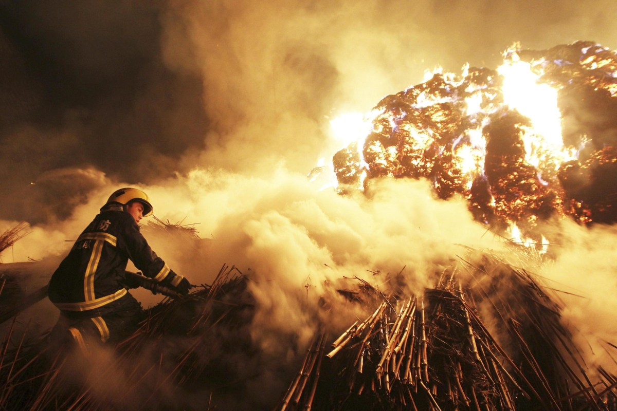 Image: A firefighter attempts to extinguish a fire which broke out on piles of reed at a paper factory in Changde
