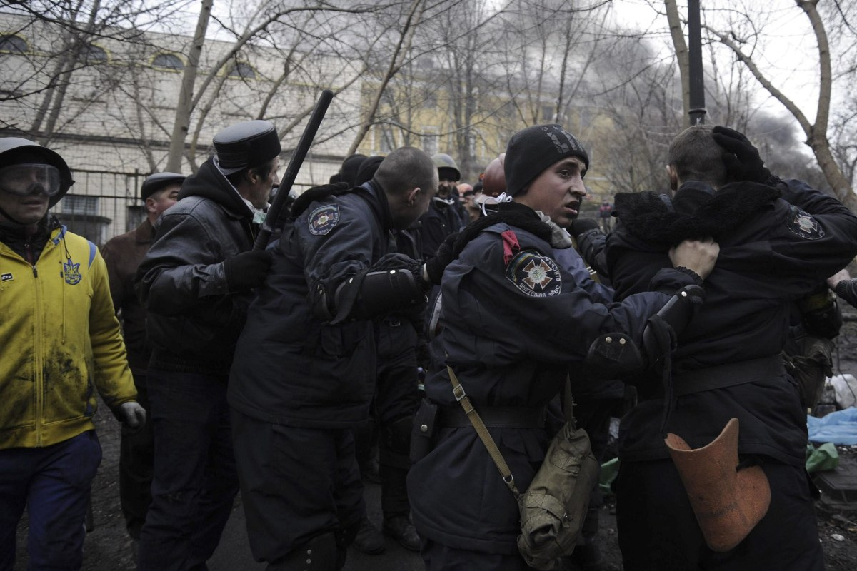 Image: Anti-government protesters lead away riot police in Independence Square in Kiev