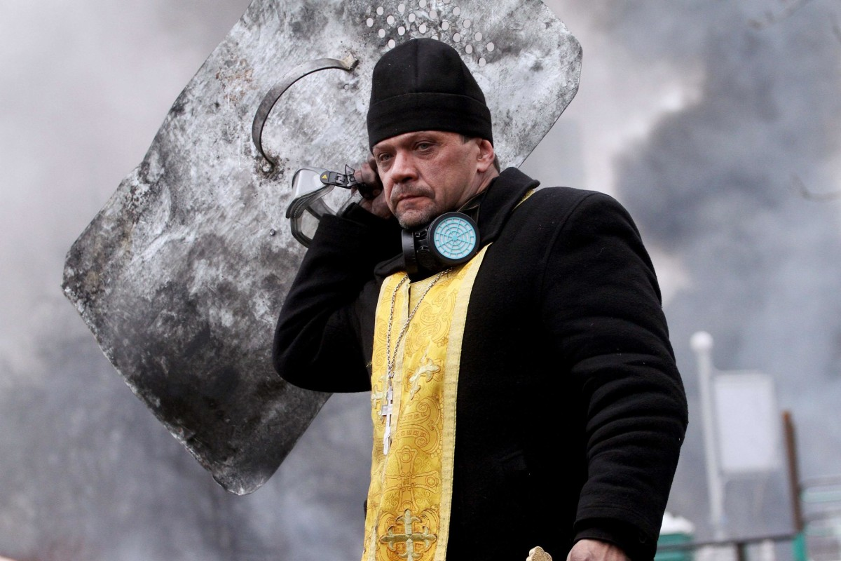 Image: A priest holds a cross and shield during clashes betwwen anti-government protesters and riot police in central Kiev