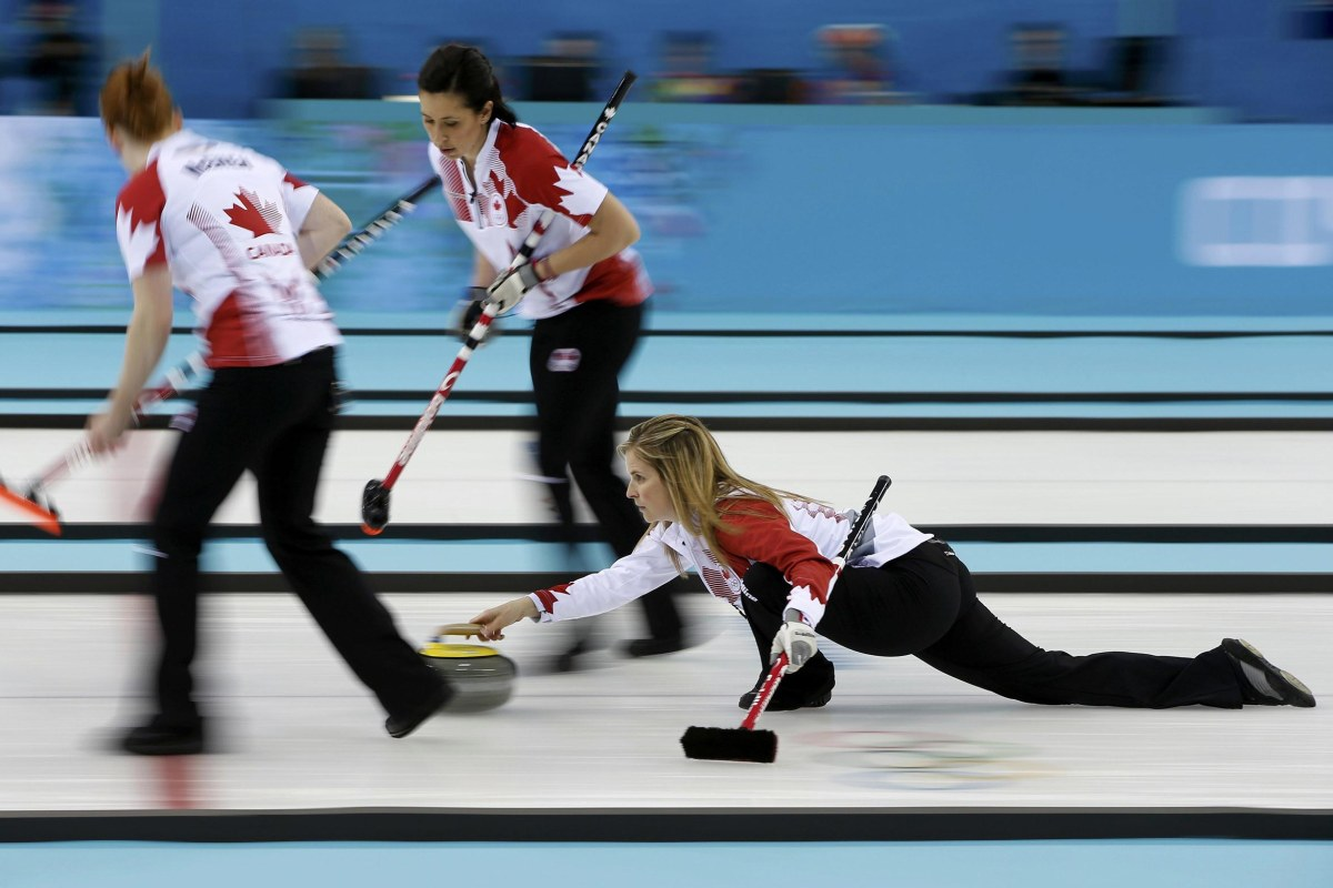 Image: Canada's McEwen and Officer prepare to sweep as Jones delivers a stone in their women's gold medal curling game against Sweden at the Ice Cube Curling Centre during the Sochi 2014 Winter Olympics