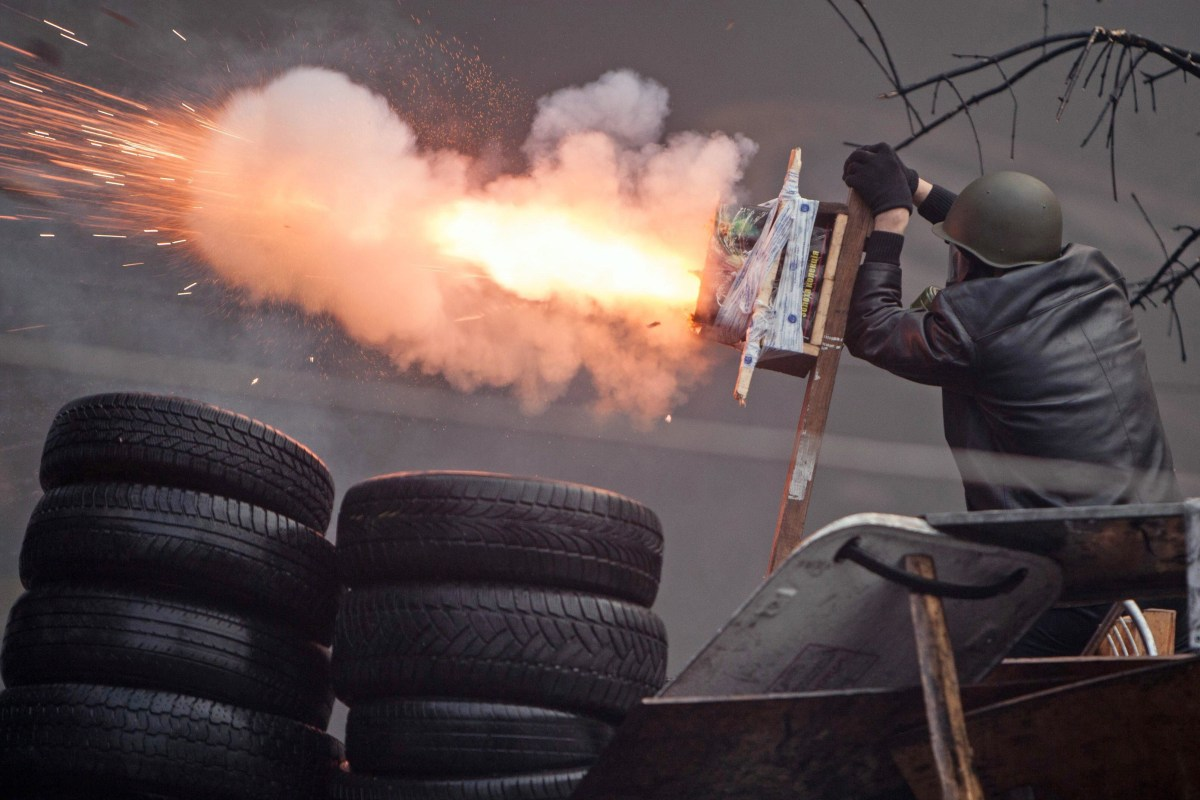Image: An anti-government protester shoots an improvised device during clashes with riot police in the Independence Square in Kiev