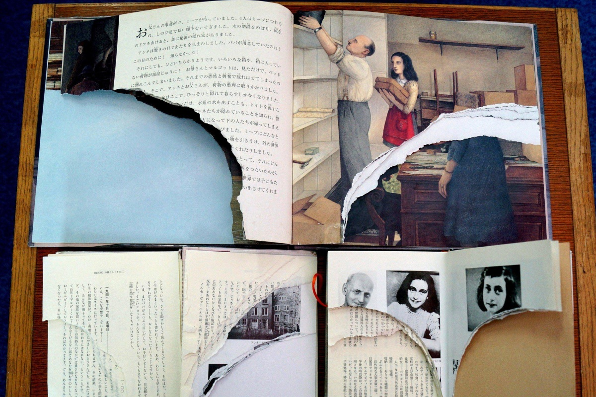 """Image: Ripped pages of Anne Frank's """"Diary of a Young Girl"""" are displayed at a library in Tokyo"""