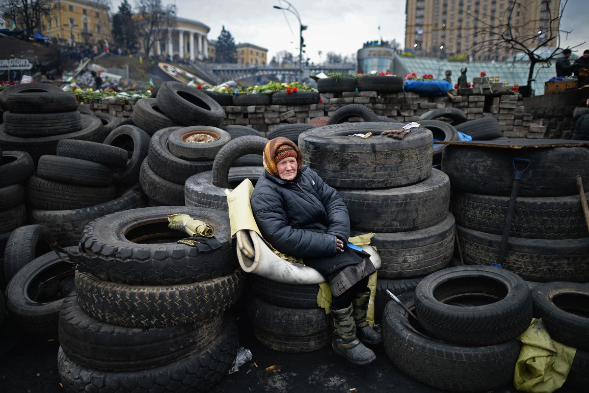Image: An elderly woman sits on tires at a barricade in Independence Square