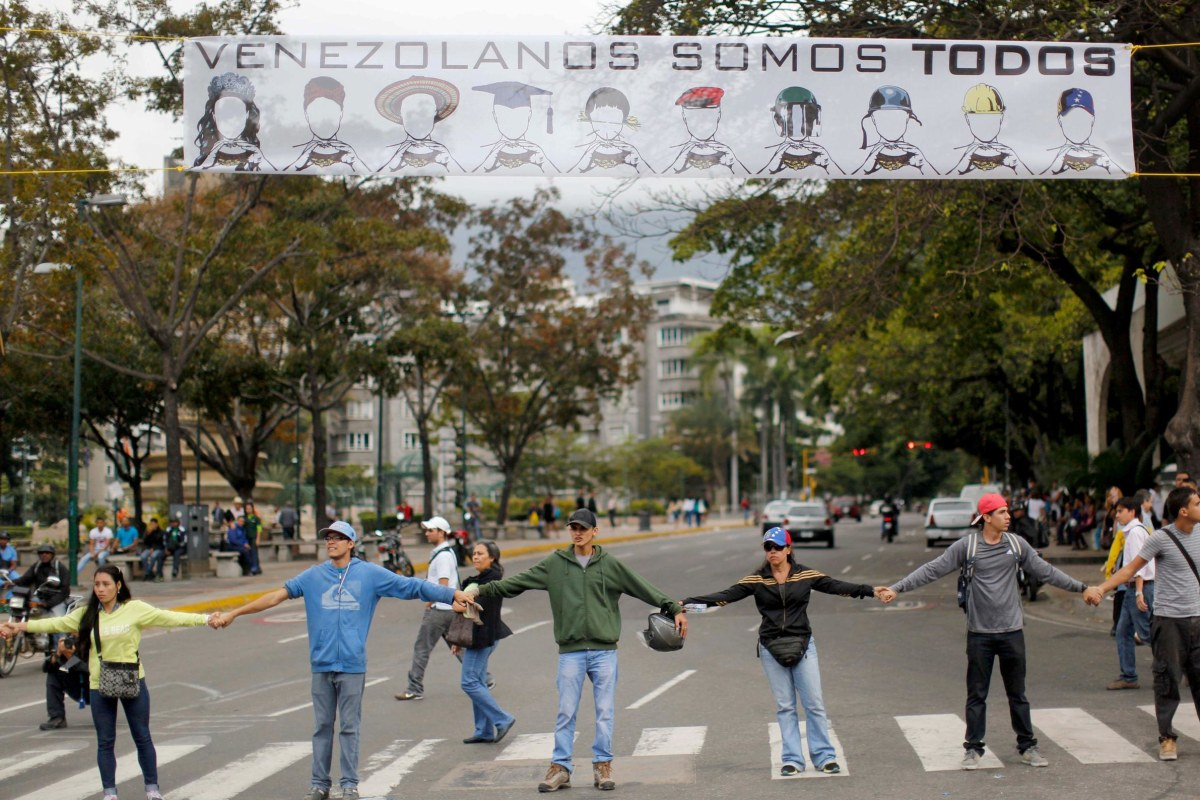 Image: Demonstrators join hands to block the highway at Altamira neighborhood in Caracas