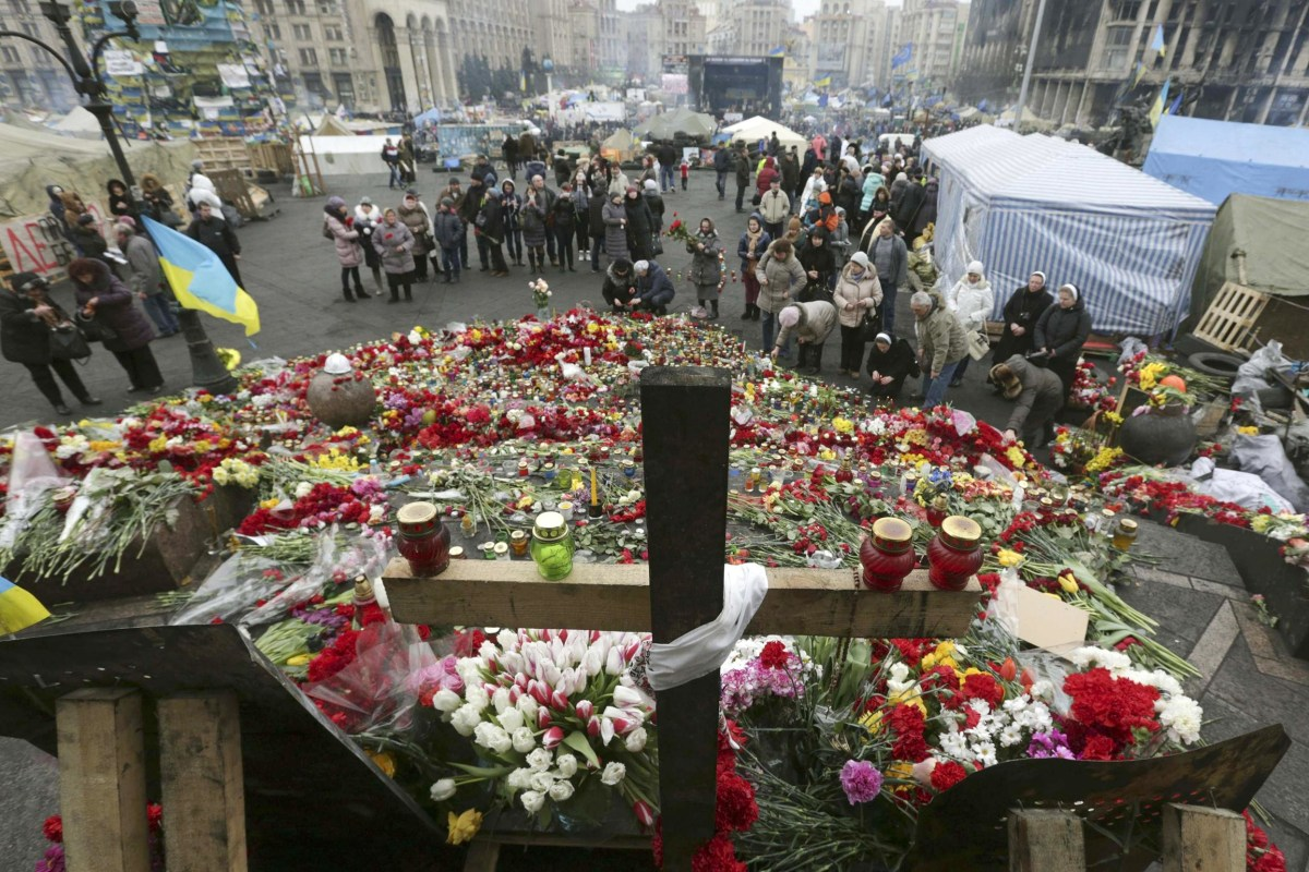 Image: People mourn at a make-shift memorial for those killed in recent violence in Kiev