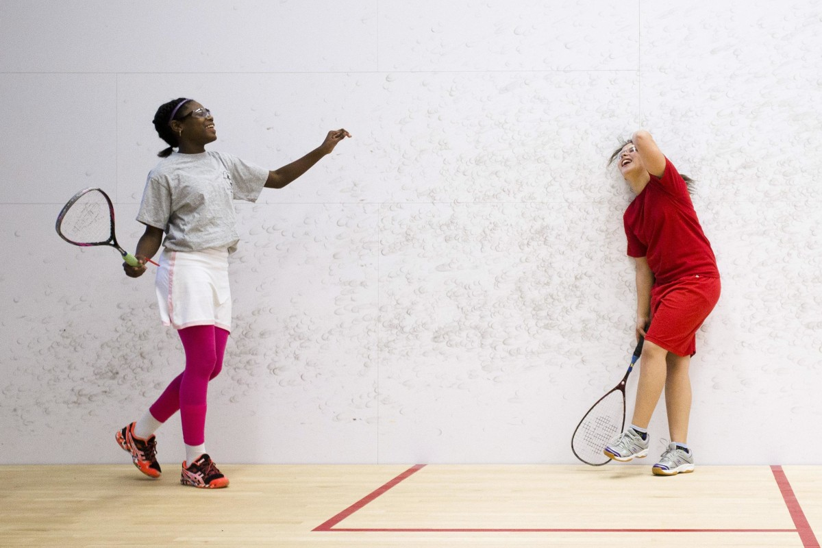 Image: Aaliyah Galloway, 12, left, and Melliah Santos, 12, laugh as they play squash at the Lenfest Center