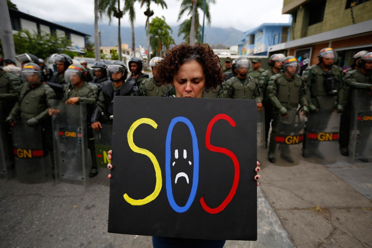 Image: A demonstrator holds a placard as she stands in front of national guards during a protest near the Cuba's Embassy in Caracas